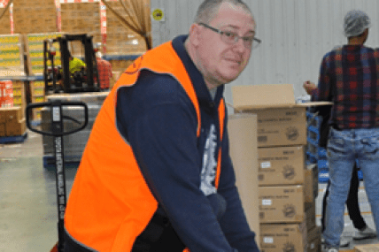 Worker in high-vis jacket is sorting boxes