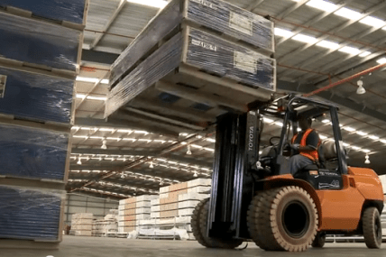 Forklift carrying pallets in a large supply room