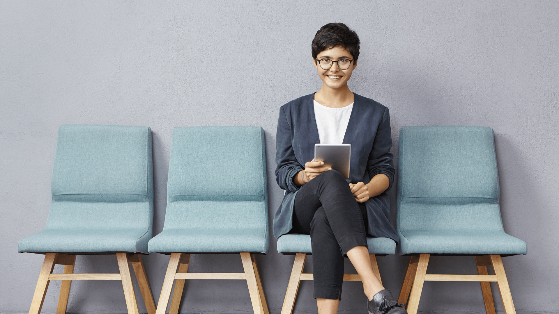 Woman sits with her tablet in a waiting room. She is smiling at the camera.