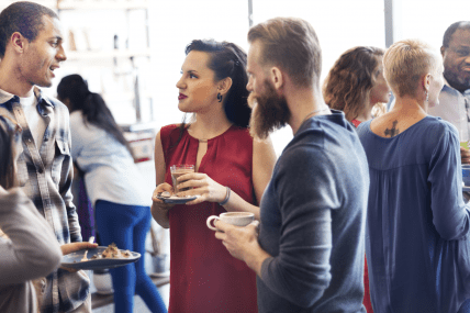 People talking in small groups at a networking event.