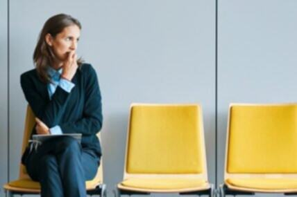 Image of a woman looking worried before a job interview. She is sitting on a yellow chair looking right, biting her nails nervously.
