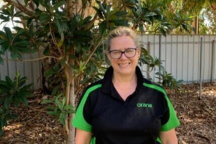 Image of Margot standing in the garden outside her workplace. She's smiling at the camera, wearing black glasses and in her black and green workers shirt.