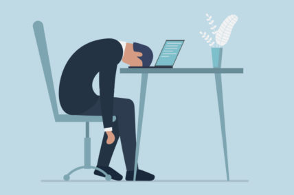 Image of a cartoon man looking deflated, sitting at his work station with his head in his laptop.