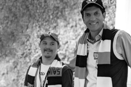 [Photo description: Lincoln is standing next to the CEO of Empirics. Both men are wearing Saint Kilda Footy Club hats, scarfs and shirts.]