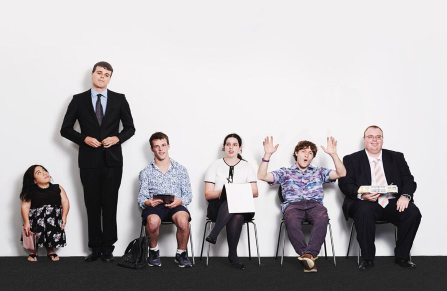 Photo of 6 job seekers shown on ABC's Employable Me sitting in a row. Paul is on the right, in a suit and holding a train.