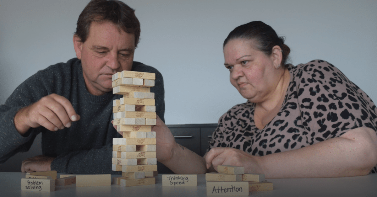 """Photo of WWtW employees, Terry and Kez, playing Jenga. Some Jenga blocks have words such as """"problem solving"""", """"attention"""" and """"Thinking speed"""" written on them to show building your mind."""
