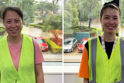Image of Thi and Hai in their workplace standing in front of a window which looks out onto a car park. Both girls are smiling at the camera, wearing bring yellow high viability gear.