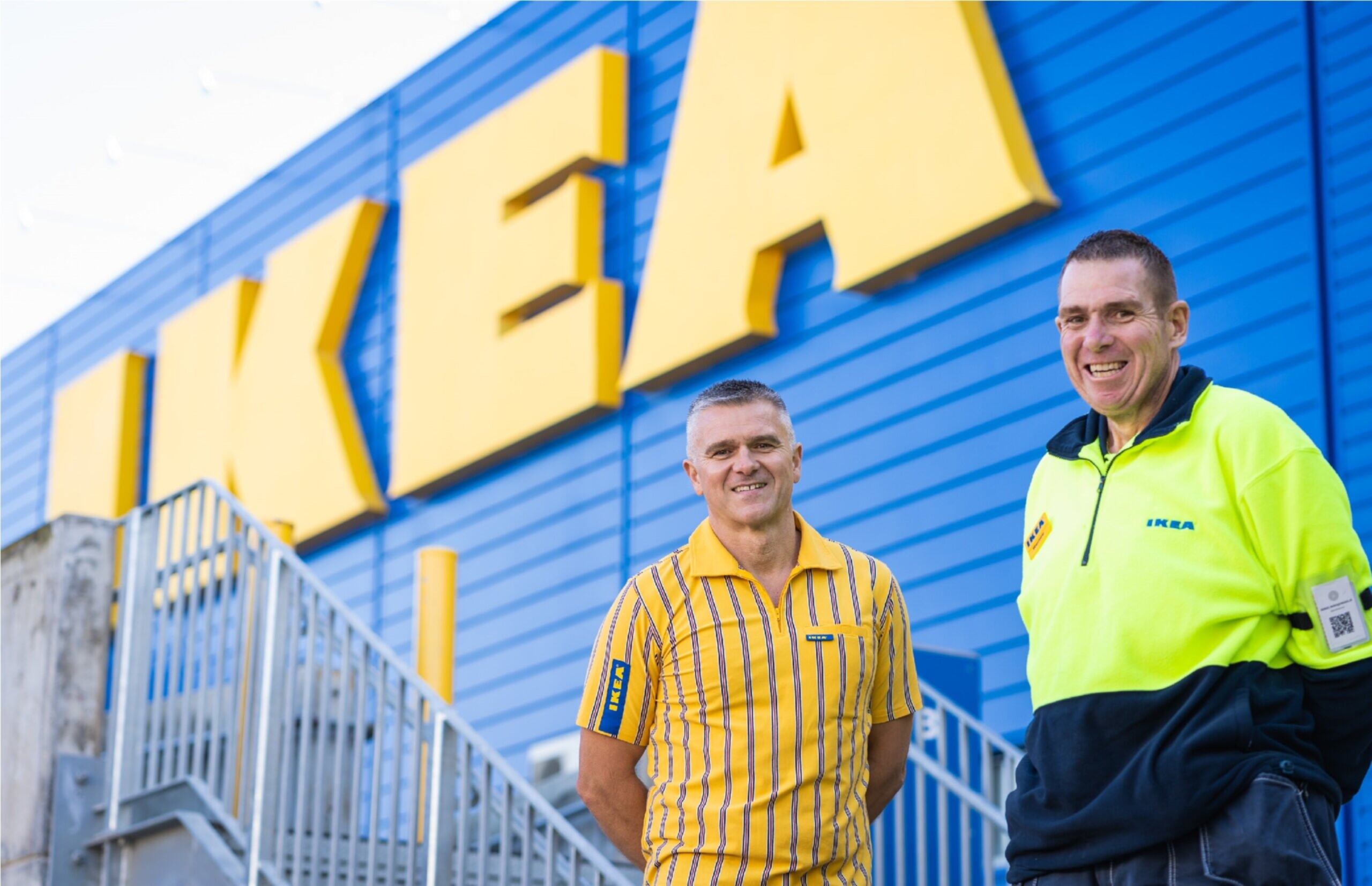 Renee stands in his high-vis IKEA jumper with his hands behind his back. He is standing outside the IKEA building and smiling at the camera.