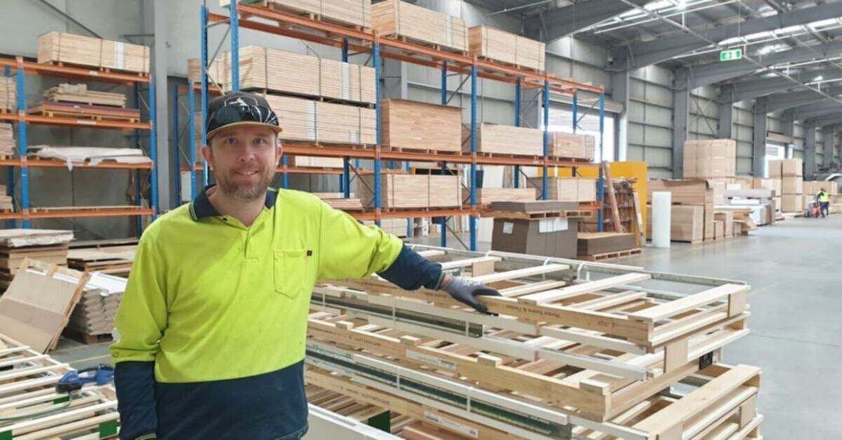Nathan is standing in the Hume Doors warehouse leaning on some wooden slacks. He's smiling at the camera, wearing a baseball hat along with a high viability yellow and blue long sleeve top and protective gloves.