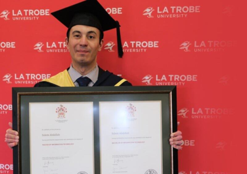 Salem is wearing his graduation clothes and cap while holding his degree in front of a red background