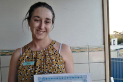 Job Seeker, Amber, is holding her TAFE Certificate and smiling at the camera