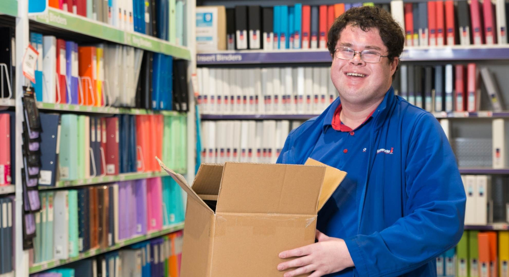 Job Seeker, Josh, is holding a cardboard box standing in the isle with all the file binders. Josh is wearing his Officeworks uniform.