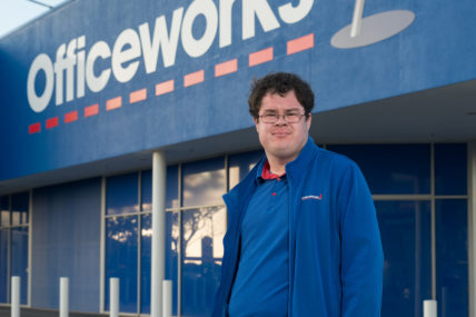 Job seeker Josh, stands outside the Officeworks store wearing his blue Officeworks uniform.