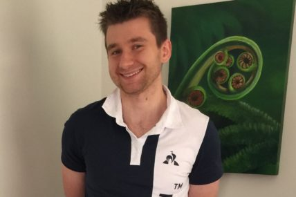 Isaac stands in a black and white polo shirt, smiling at the camera.