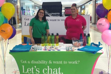 Two WISE staff members stand at a WISE pop-up stand inside a shopping centre.