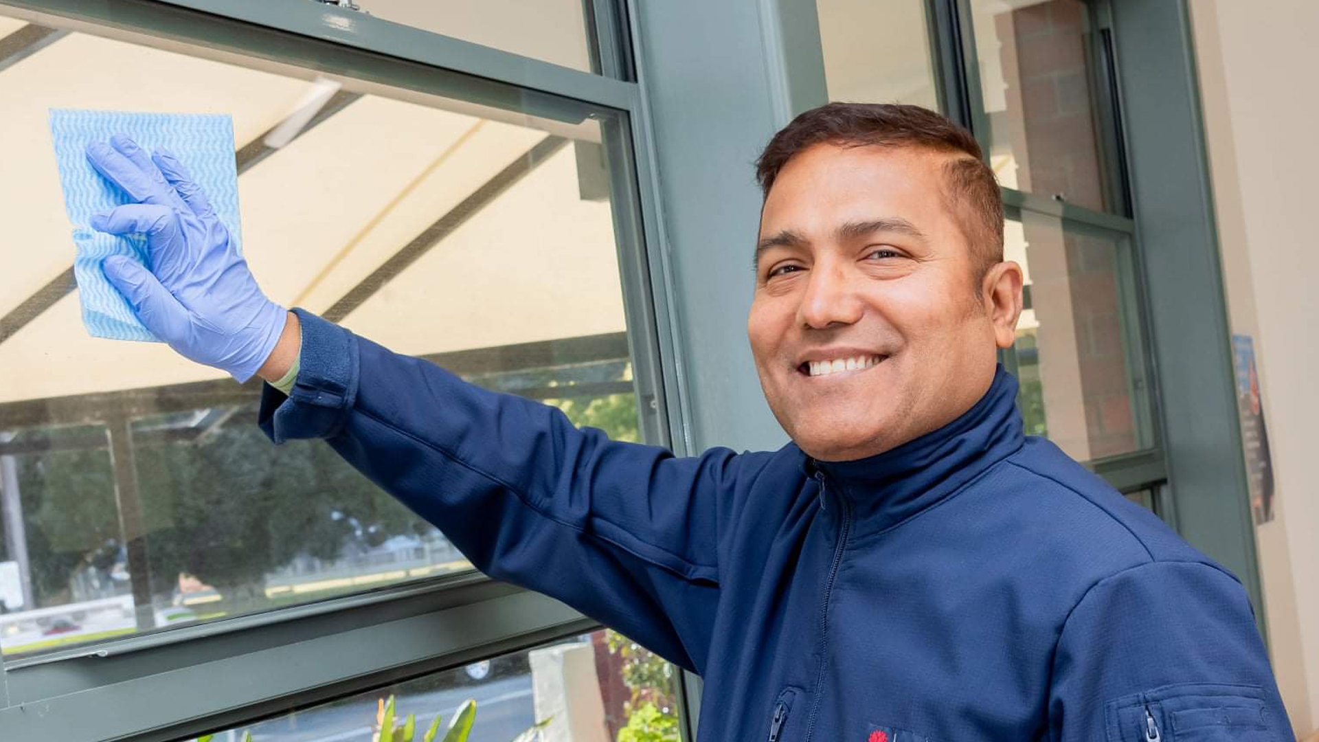 Image features Farhad in his new work uniform, smiling at the camera while cleaning a window.