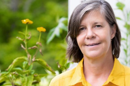 Woman wearing a yellow polo shirt is smiling at the camera. She is standing in a garden.