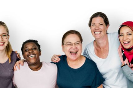 Five women of different ages, backgrounds and heights are laughing together with their arms around each others shoulders