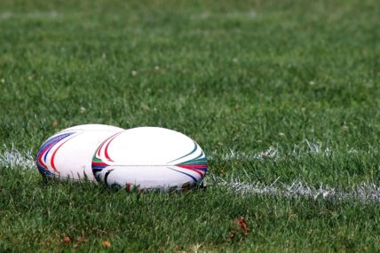 Two rugby balls sit on a try line.