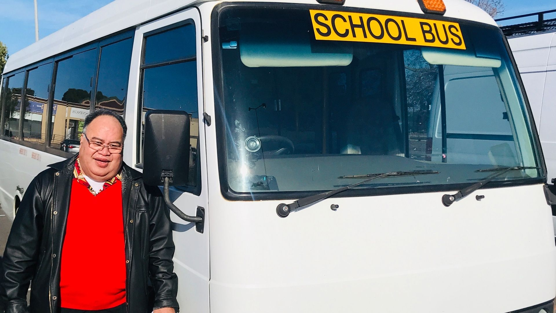 Fea stands beside the bus he drives. He is wearing a bright red jumper and smiling at the camera