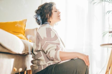 Woman is meditating on the floor of her living room