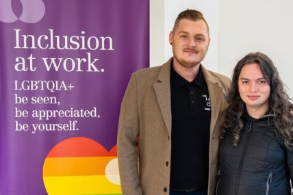 Rainbow WISE customer Skylar, and Rainbow WISE Diversity Consultant Jake, stand side by side in front of a Rainbow WISE banner