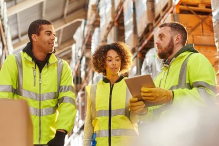 Three workers are standing together in a meeting. They are wearing high-vis gear and standing in a warehouse full of boxes
