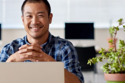 Middle age man smiling behind a laptop at his desk