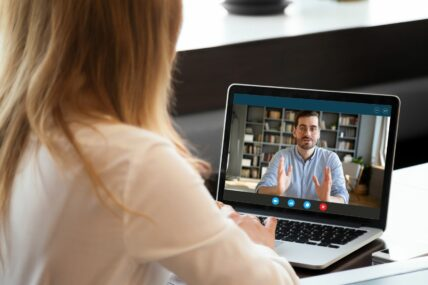 over the shoulder shot of a woman interviewing a man over video call