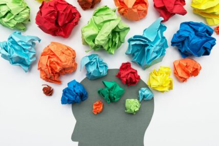 Mind with many ideas coming out of it. Ideas are in the formed of coloured tissue paper srunched into balls
